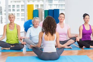 36422902 - group of people practicing lotus position in yoga class