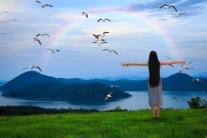 17751655 - girl standing with open arms against the blue sky with rainbow